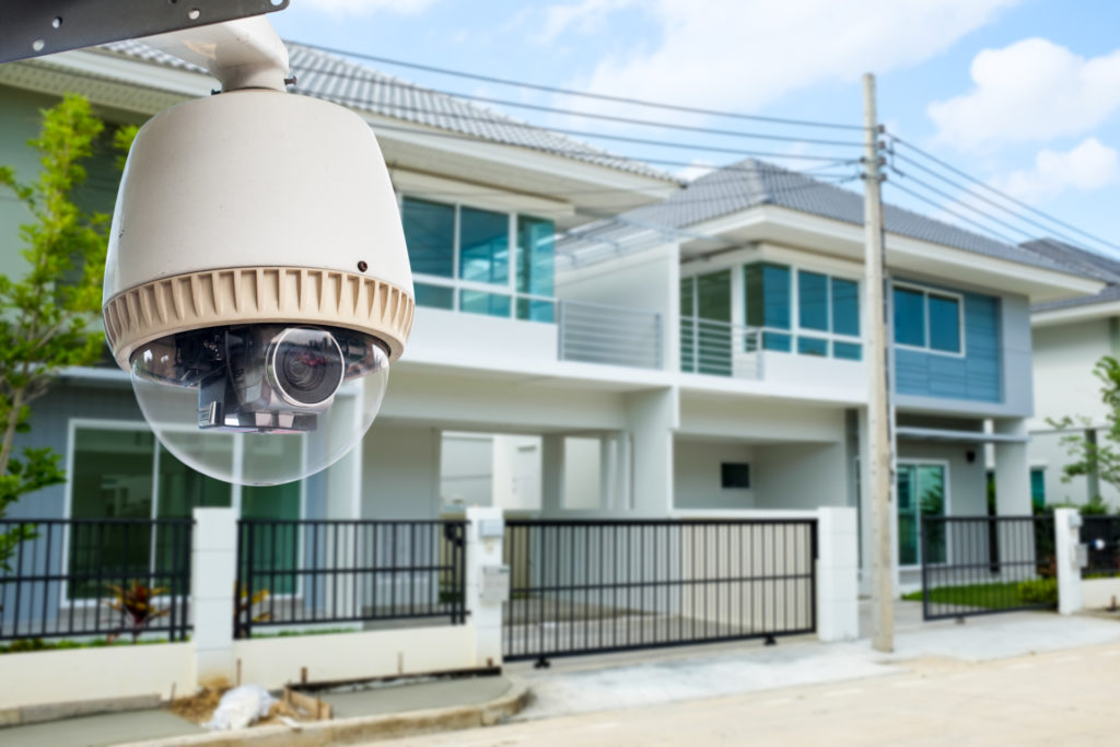 CCTV Camera or surveillance operating with house village in background